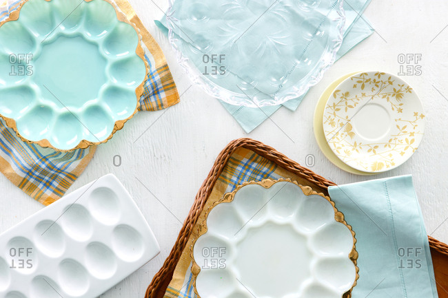 High angle view of egg shaped empty plates with napkins and tray on table at home