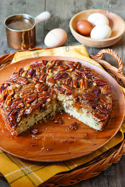 High angle view of pecan cake served in plate with eggs and syrup on wooden table at home