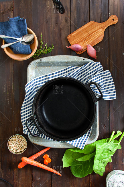 Overhead view of empty cooking utensil with vegetables on table at home
