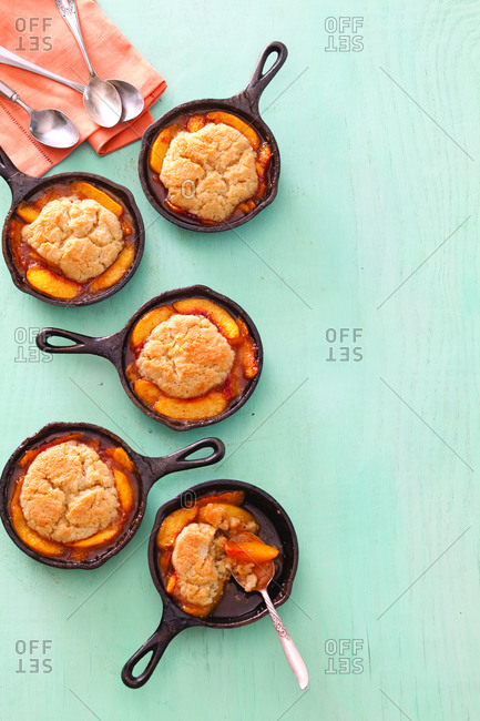 High angle view of baked peach cobblers in cooking pans on table at home