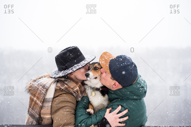 Couple hugging and kissing puppy outside during snowfall