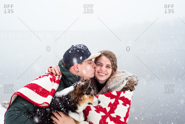 Girl huddled in blanket with guy & dog gets surprise kiss on the cheek