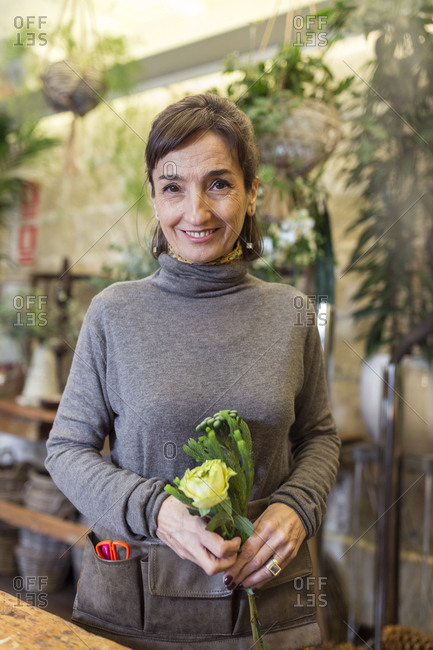 Peaceful happy senior woman holding flowers at flower shop desk