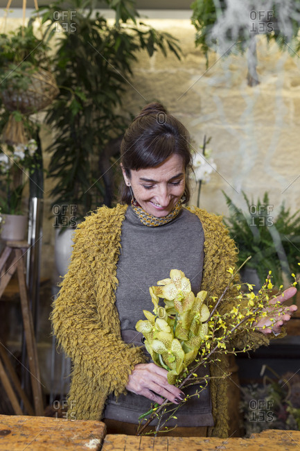 Portrait of cheerful woman holding yellow flowers at slower shop