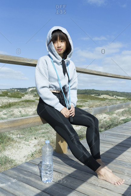 Sporty Asian Chinese woman relaxing holding jumping rope