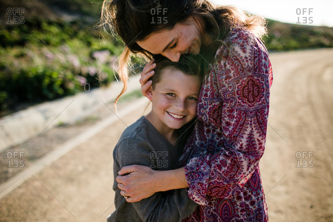 Mom and son hugging while son smiles in southern California