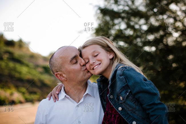 Dad giving daughter kisses in SoCal
