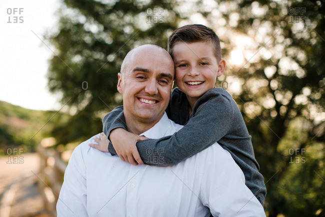 Father and son hugging and smiling at camera in SoCal