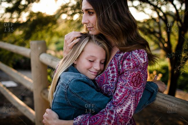 Mom hugging daughter while daughter smiles in SoCal