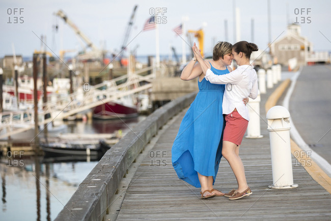 A same sex couple dances and smiles on wharf.