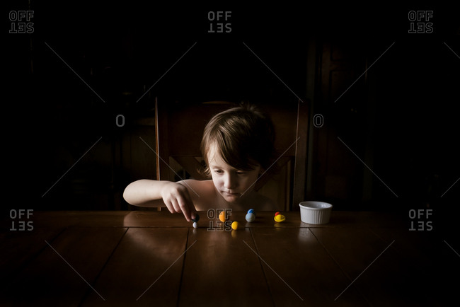 A young small boy at a table with planet eraser toys