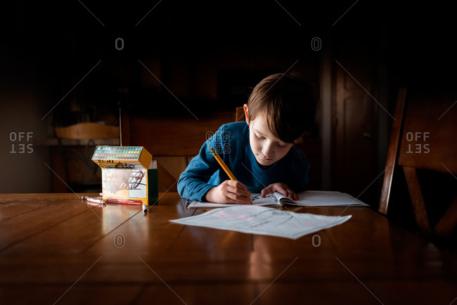 A young small boy doing homework at a table