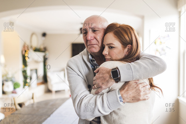 Portrait of father hugging adult daughter with tears in his eyes