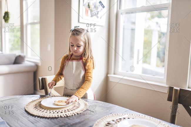 Little girl in apron flipping pancake at breakfast table