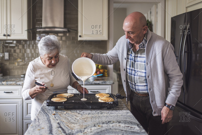Great grandma cooking pancakes with her adult son
