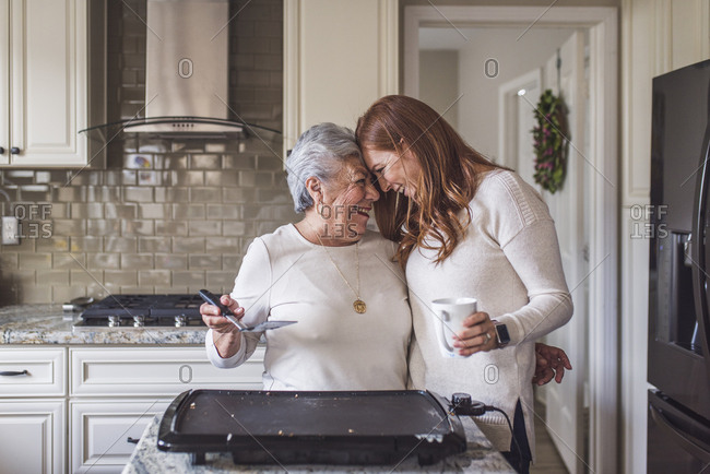 Senior woman and adult granddaughter cooking pancakes for breakfast