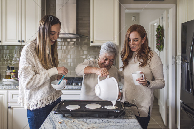 Senior woman and adult granddaughters cooking pancakes for breakfast