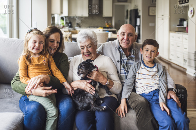 Multigenerational family and small dog sitting on living room couch
