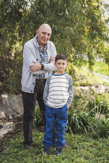 Portrait of grandfather and grandson standing outside in park