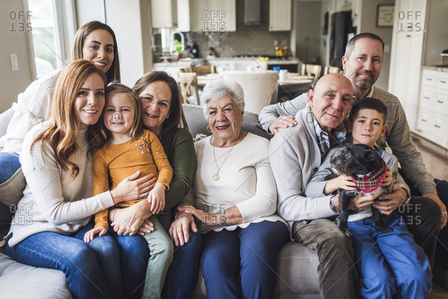 Portrait of multigenerational family sitting on living room couch