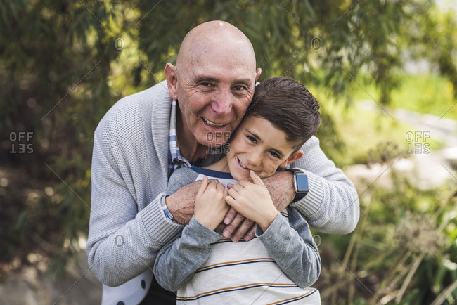Close up portrait of grandfather and grandson hugging outside