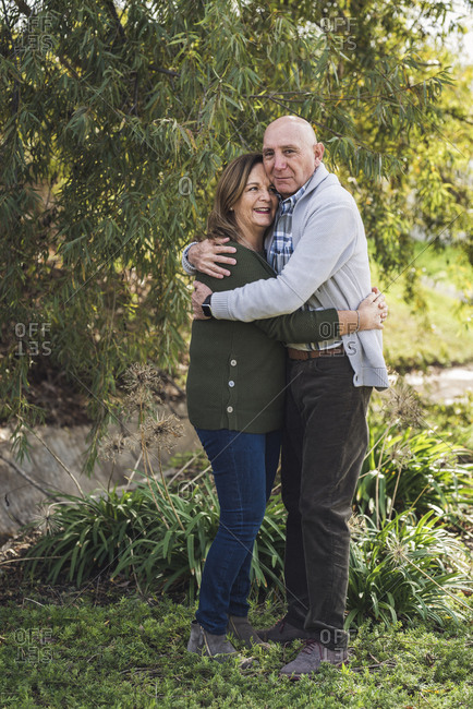 Portrait of grandfather and grandmother embracing outside