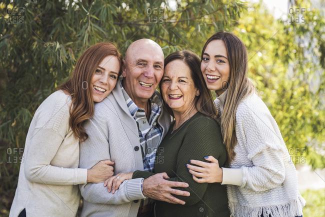 Portrait of multigenerational family hugging outside