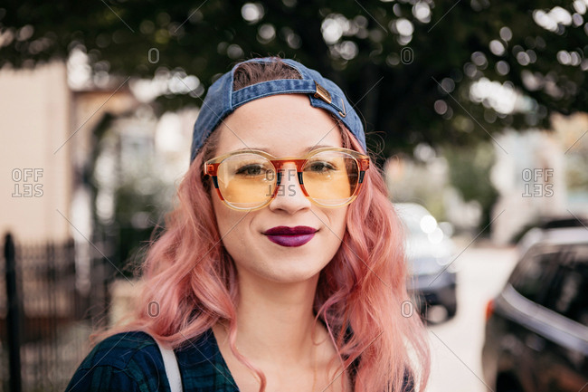 Young millennial strolls downtown street in yellow sunglasses