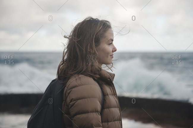 Young smiling woman with windy hair looking at the stormy ocean