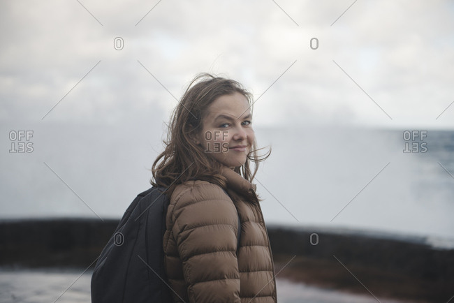 Young woman with backpack and windy hair on seafront looking at camera
