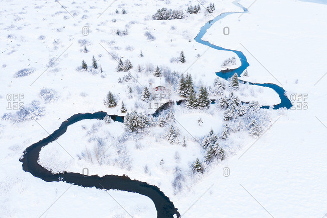Building near river between trees and fields in snow