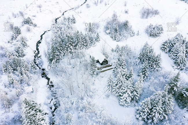 Lonely building near river between trees and fields in snow