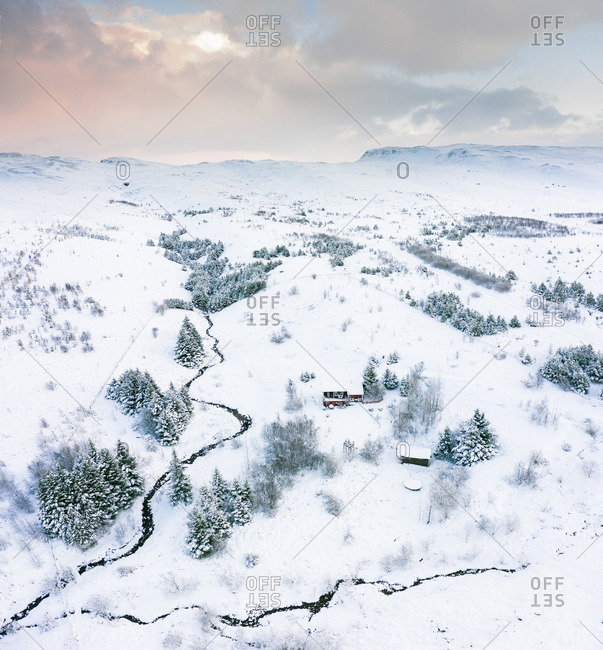 Buildings near river between trees and fields in snow