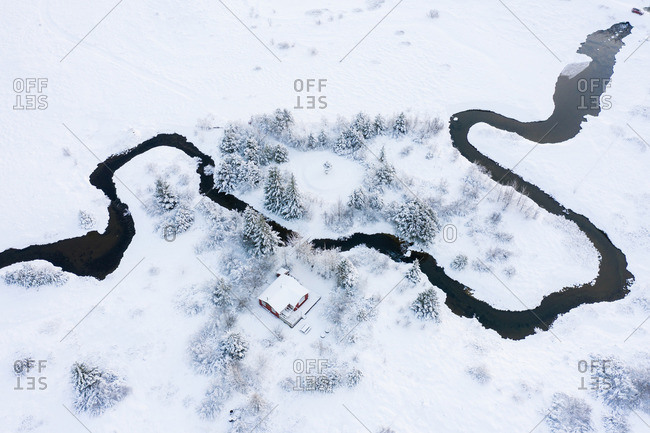 Lonely country house near river between trees and fields in snow
