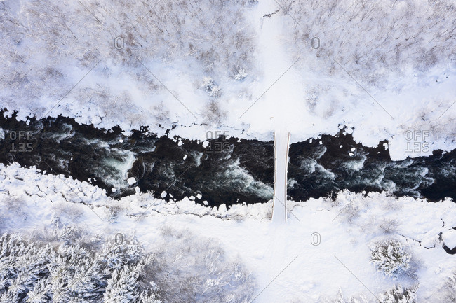 Road with bridge above river between trees and field in snow