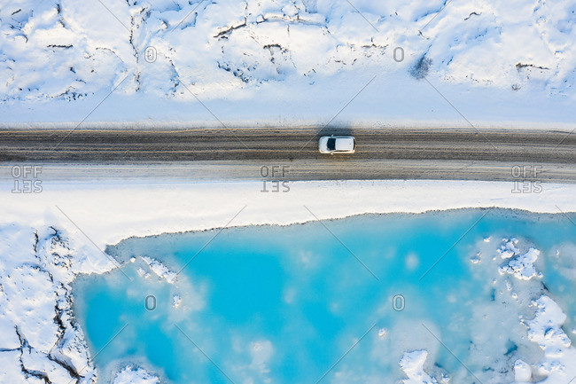 Auto on road near azure water of river between snow