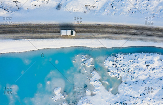 Automobile on road near azure water of river between snow