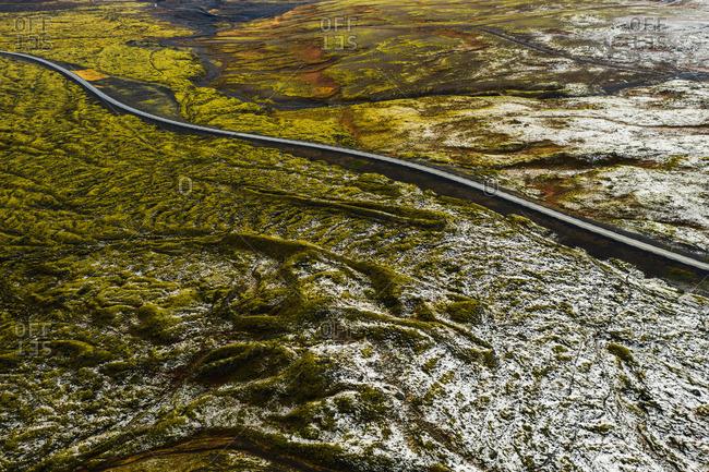Road between green fields in snow