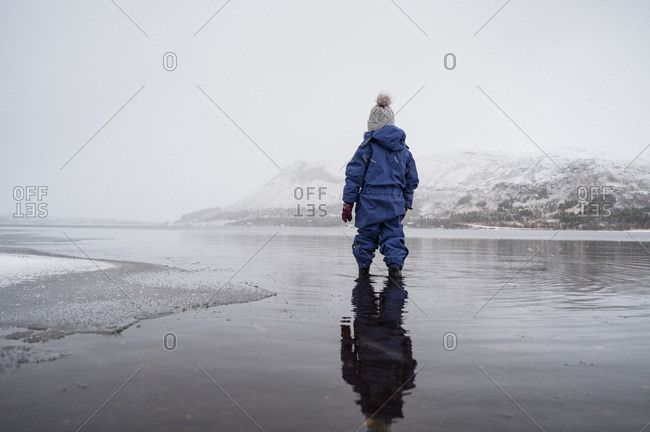 Child standing in water near hills in snow on shore