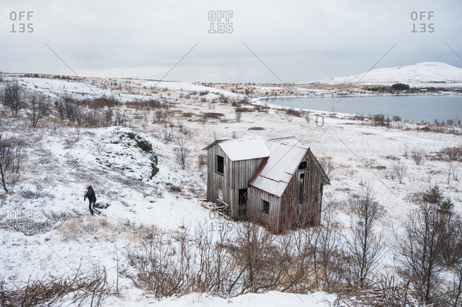 Man and deserted cabin between field near water