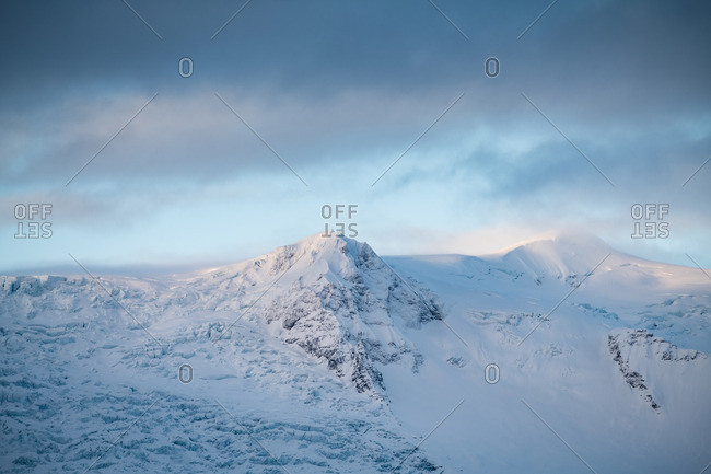 Tops of stone mountains in snow and cloudy sky