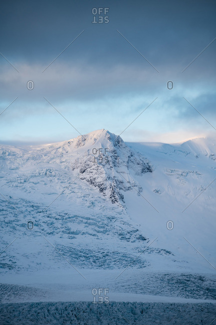 Peaks of stone mountains in snow and cloudy sky
