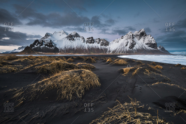 Black soil of lands near water and tops of stone mountains in snow