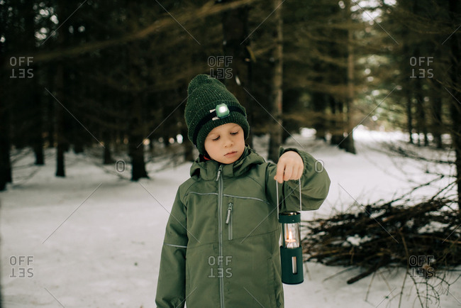 Boy standing in a snow covered forest holding lantern & torch thinking