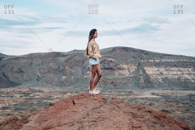 A woman stands on a rock formation against a mountain backdrop