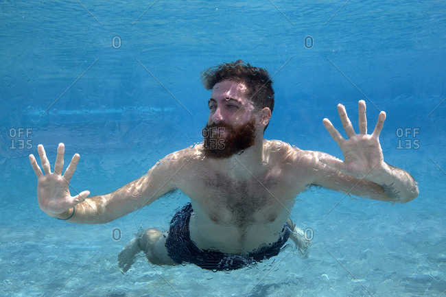 Man swims in glass pool on vacation