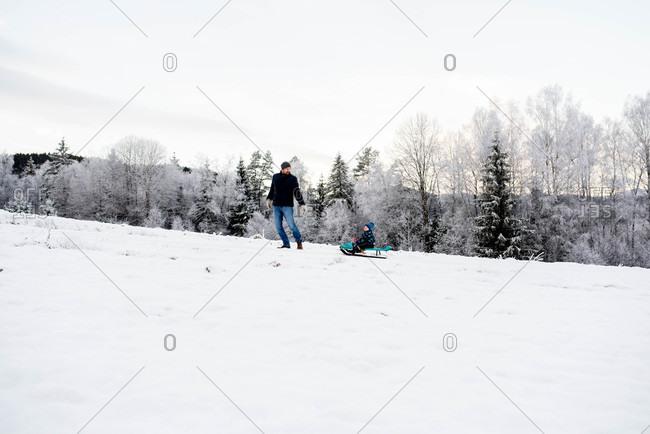 Father son walking sledging in snow white forest winter wonderland