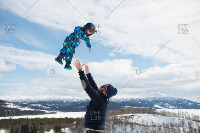 Father son playing in snowy mountain in winter wonderland