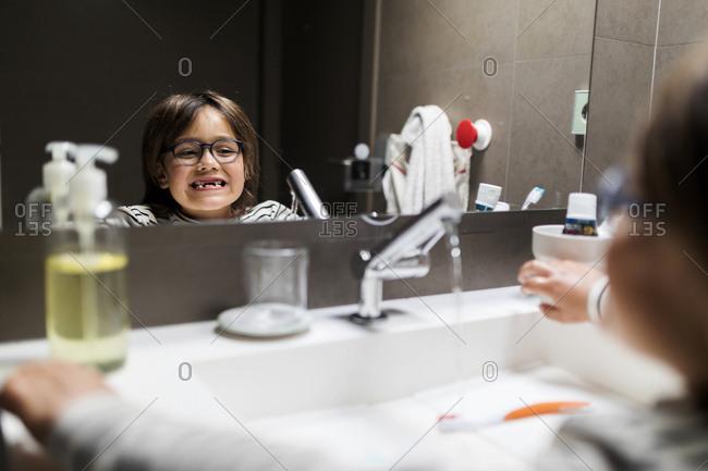 Boy on striped top brushing his teeth