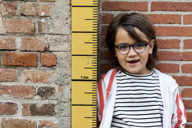 Child in striped top being measured on a keepsake measuring stick